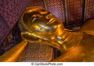 Golden lying buddha in Wat Pho in Thailand - Close up golden...