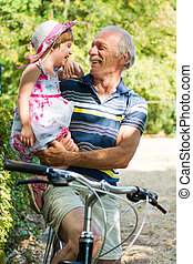 Grandpa laughing on bicycle with granddaughter - Grandpa...
