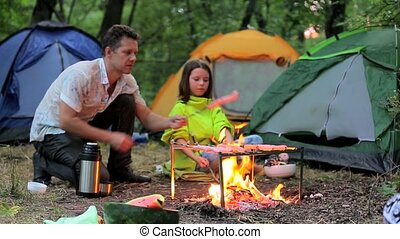 Late evening in camp, father and daughter sitting by the...