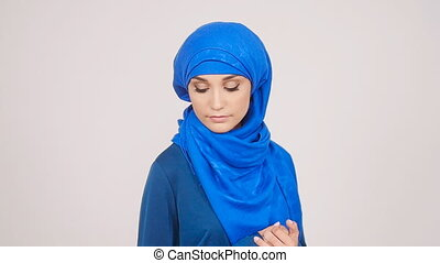 Beautiful young muslim woman posing in studio on white...