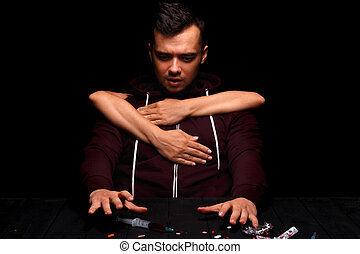 A junkie trying to take a syringe with drugs. A drug addicted on a black background. Hands keeping a boy from the drug injection.