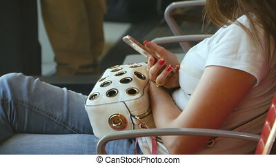 Woman uses a smartphone in airport waiting lounge....