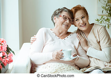 Woman hugging her friend - Young woman nurse smiling and...