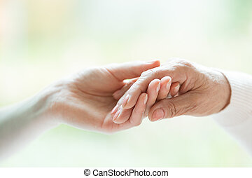Young hand holding older one