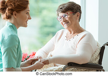 Woman in wheelchair - Young caucasian nurse supporting elder...