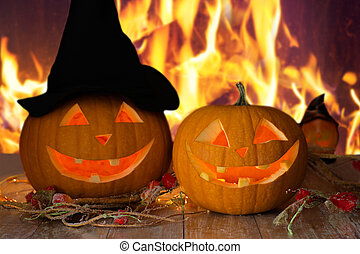 carved halloween pumpkins on table over fire - holidays,...
