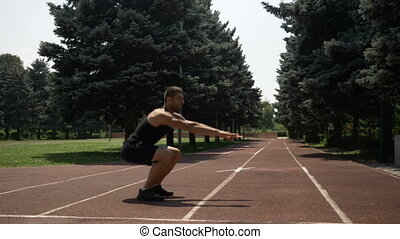 Athlete runner preparing for competition doing squats