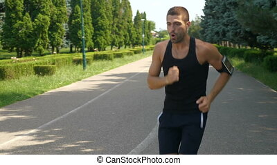 Handsome athletic man training on running track using...