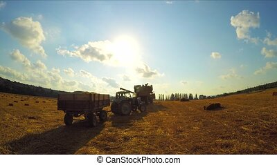 Tractor and combine harvester leave the field after agricultural work