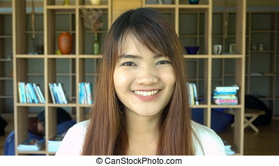Portrait of smiling beautiful asian student standing in...