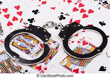 Handcuffs with things gaming - playing cards on a white...