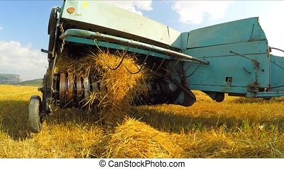 The combine harvests straw and forms it into square bales of hay, discards them on the field