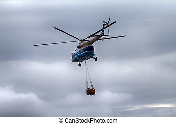 Helicopter carries sling (rope mesh) with empty metal...