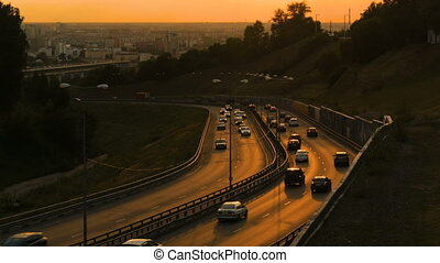 City traffic on the road at sunset