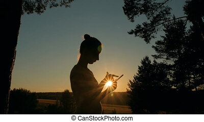 Woman using smartphone in park at sunset - Woman silhouette...