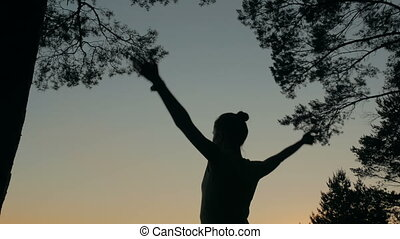 Woman silhouette practicing yoga in forest after sunset -...