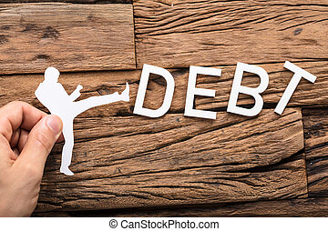 Paper Cut Out Figure Kicking The Debt Word - Hand Holding A...