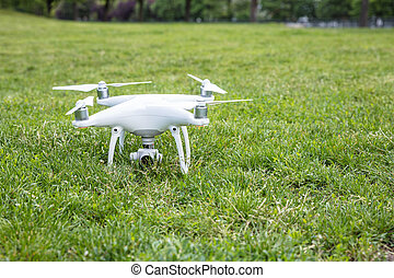 Closeup of white drone on grassy field in park