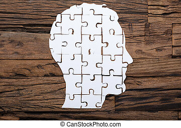 Businessman's Head Made From Paper Jigsaw Puzzle Pieces On Table