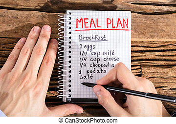 Person Making Meal Plan On Notebook