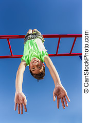 Upside down on the monkey bars. - A happy young boy hangs...