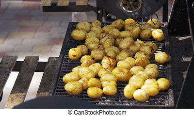 Young potatoes prepare on a grill. Hand Using Tongs For...