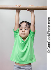 Asian Chinese little girl hanging on horizontal bar in...