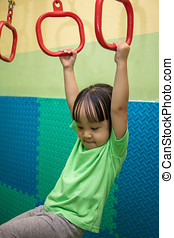 Asian Chinese little girl hanging on rings at indoor...