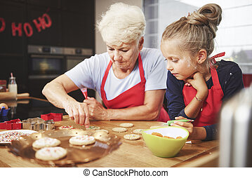 Senior and girl preparing christmas cookies