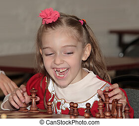 Smilling - Child 7 years old at chess competition