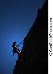 Courage - A climber hangs from a thread on the side of a...