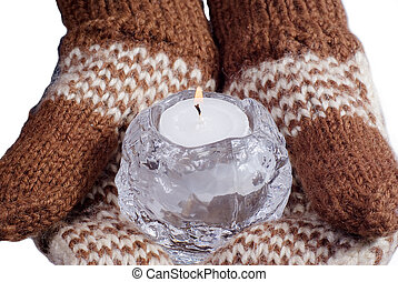 Two hands dressed in mittens hold a burning candle