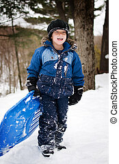 boy with a sled - young child with a sled outdoors in winter