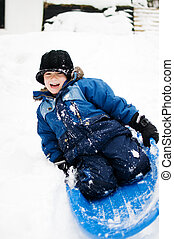 sleding - young boy riding a sled down a hill