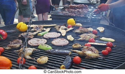 Cooking of Meat and Vegetables on the Grill. Hand Using...