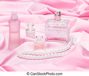 Perfume bottles surrounded by silk fabric - Perfume bottles...