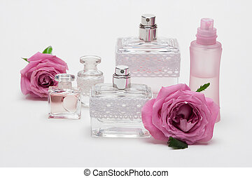 Perfume bottles with rose flowers on light background -...