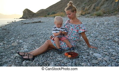 Evening, sea beach. The son sits on his mother's lap and...