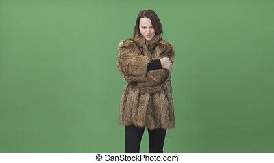 Young brunette woman demonstrating fur coat, stroking the...