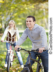 Walk on bicycles - Couple cycling in autumn park