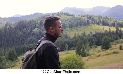 Guy tourist walking on a mountain road