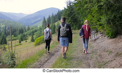 Three tourists stroll along the mountain road near the forest