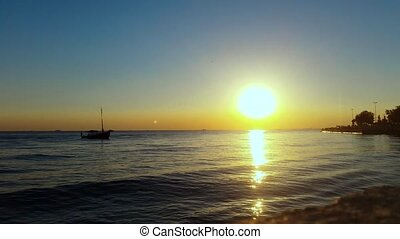 Boat floating on the calm sea at sunset
