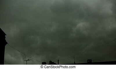 Gray clouds thicken over the city. They are like steam or...