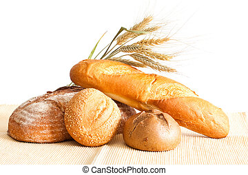 Fresh bread - Group of bread and wheat spikes on a white...