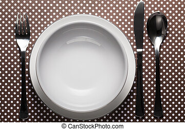 Gray bowl on white plate with fork, knife and spoon on dots cardboard. Flat lay with copy space.