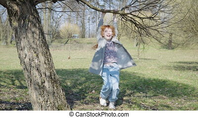 Red-haired girl is playing in a sunny park - Little girl is...