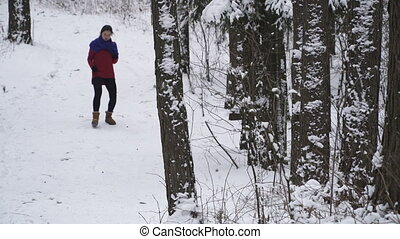 woman running in the winter forest - Young woman in a red...