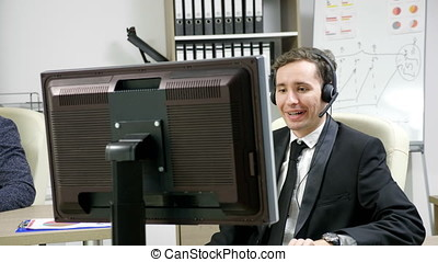 Telemarketing operator using headset to talk on the hot line...