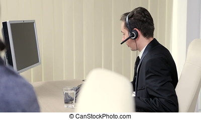 Businessman using headset to talk on the hot line with...
